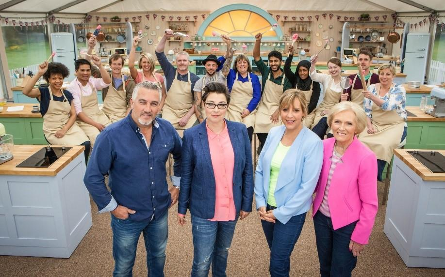 Paul, Sue, Mel, and Mary are the hosts and judges of GBBO. The bakers are behind them.