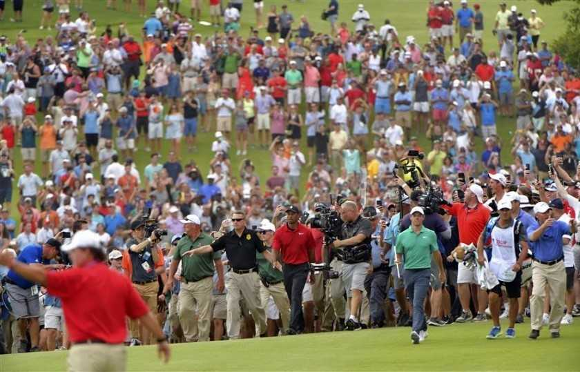 Tiger+in+red+in+escorted+by+his+thousands+of+fans+just+moments+before+he+wins+the+championship.