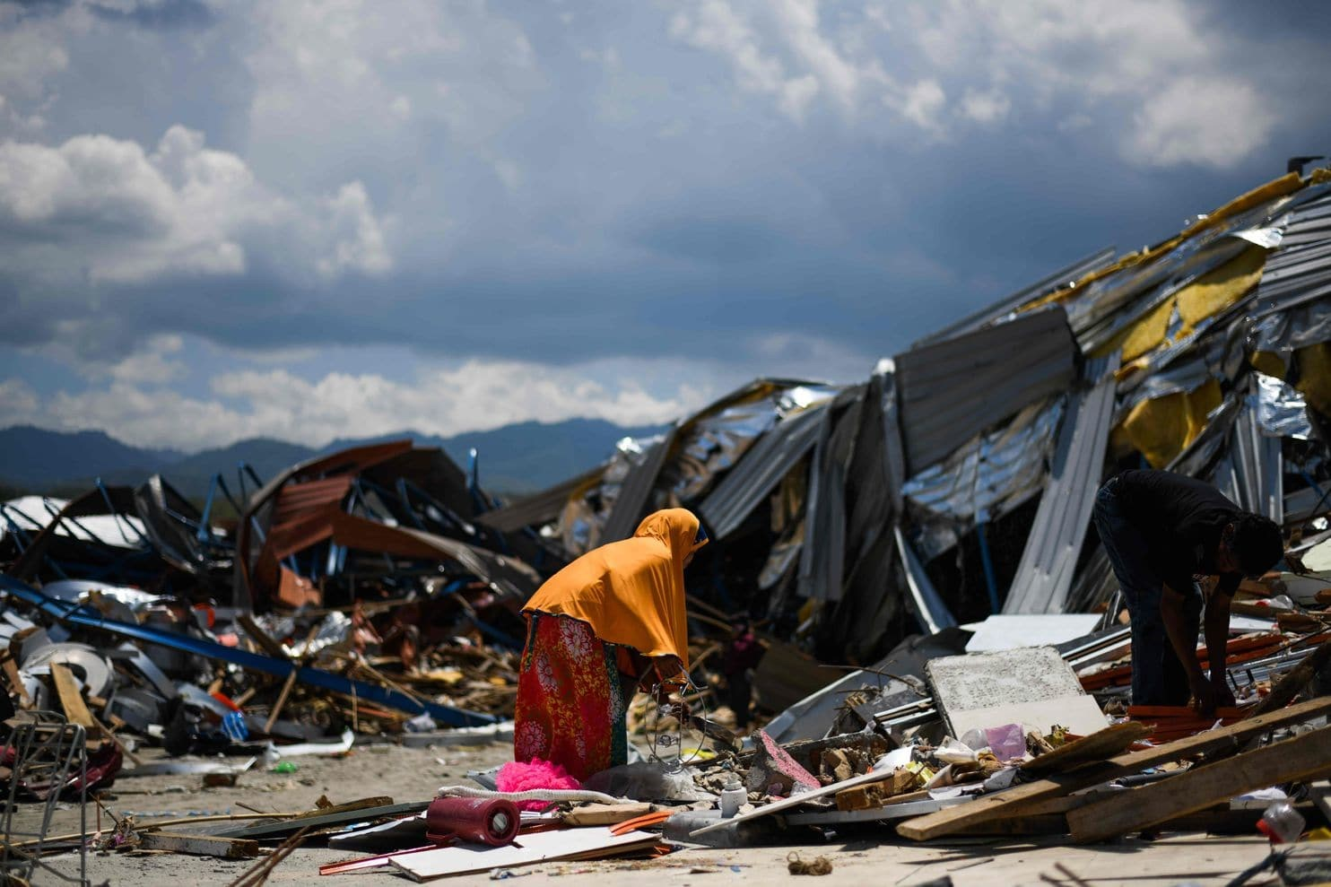 A woman searches for supplies amongst debris after a massive earthquake struck the city of Palu.
