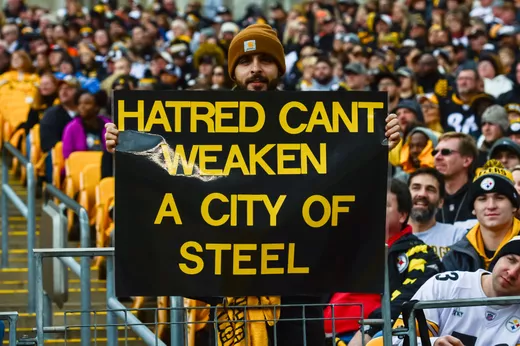 A fan from Steelers game following the shooting holds a sign showing the unity of Pittsburgh.