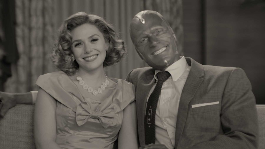 Two of the strongest Avengers are shown one being Scarlett Witch (Wanda Maximoff) and the other Vision. This is a picture from their tv show known as Wanda Vision. They are both smiling as they are a happy couple in what appears to be the 70s.