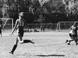 Running down the sidelines to attempt to score a goal.
