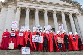 Women dressed as handmaids stand outside of a legislative building advocating for the